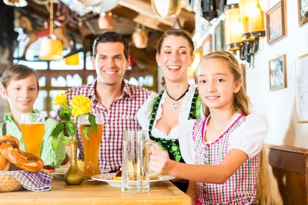 Bayerisches mädchen, das dirndl trägt und mit familie im traditionellen restaurant isst