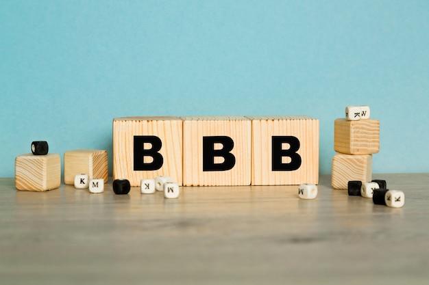 Bbb wort aus holzbuchstaben auf blauem hintergrund