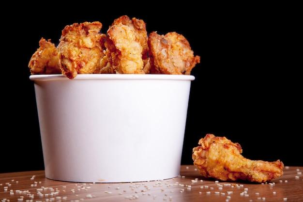 Bbq chicken wings in einem weißen eimer auf einem holztisch und einem schwarzen hintergrund.