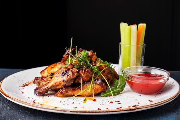 Bbq chicken wings serviert mit ketchup, sellerie und karottenstäbchen