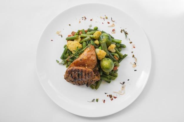 Bbq-fleisch mit gemüse auf einer weißen platte. gesundes konzept