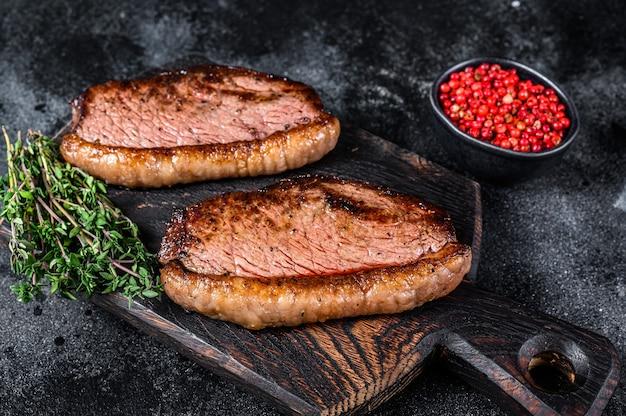 Bbq gegrillte lendenstückkappe oder picanha-steak auf einem hölzernen schneidebrett.