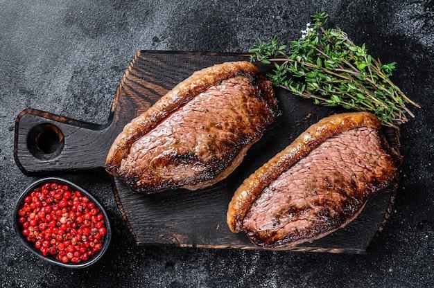 Bbq gegrillte obere lendenkappe oder picanha-steak auf einem hölzernen schneidebrett auf holztisch. draufsicht.