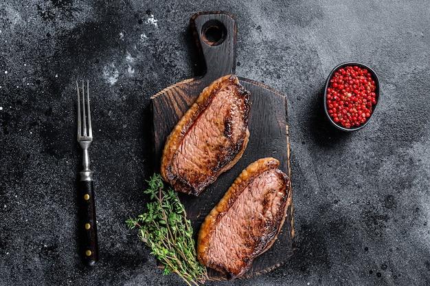 Bbq gegrilltes top lendenstück oder picanha-steak auf einem holzbrett. schwarzer hintergrund. ansicht von oben.