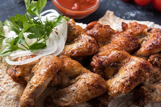 Bbq hühnerflügel mit roter sauce. nahansicht