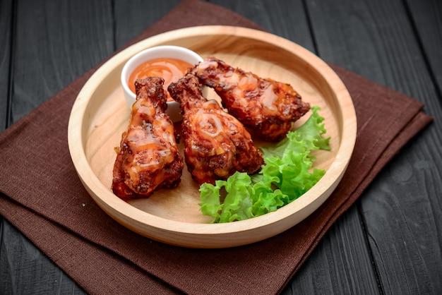 Bbq hühnerflügel mit würziger chilisauce auf einem holzteller