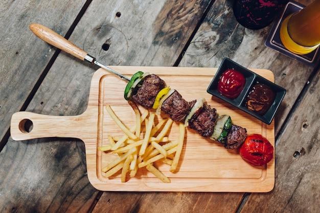 Bbq-rindfleisch-kebab diente mit pommes-frites, tomatensauce und bbq-soße auf hölzerner platte.