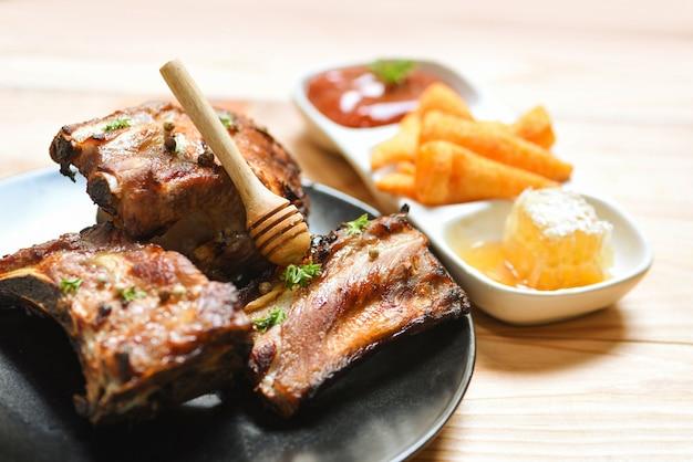 Bbq-schweinerippchen, gegrillt mit honigsüßer soße und kräutergewürzen, auf dem tisch serviert gebratenes barbecue-schweinerippchen in scheiben geschnitten