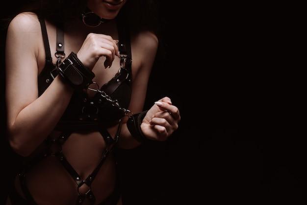 Bdsm. mädchen in handschellen und sexy schwarzer lederunterwäsche