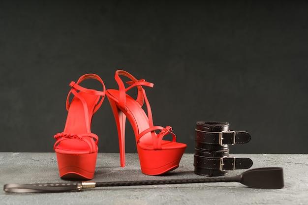 Bdsm-outfit für sexspiele für erwachsene. rote hochhackige striptease-schuhe und handschellen, peitsche auf dunklem hintergrund - bild