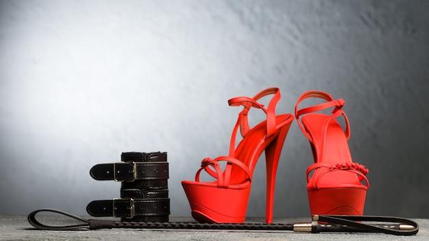 Bdsm-outfit für sexspiele für erwachsene. rote hochhackige striptease-schuhe und handschellen, peitsche auf dunklem hintergrund