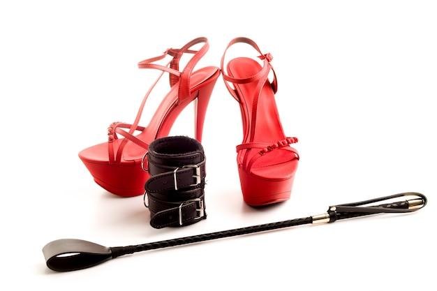 Bdsm-outfit für sexspiele für erwachsene. rote hochhackige striptease-schuhe und handschellen, peitsche lokalisiert auf weißem hintergrund