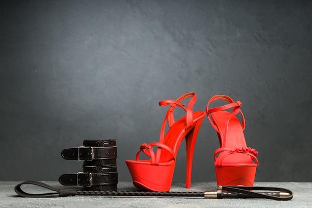 Bdsm-outfit für sexspiele für erwachsene. rote hochhackige striptease-schuhe und handschellen