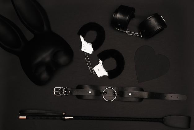 Bdsm-spielzeugset für erwachsene. peitsche, handschellen, maske. draufsicht.