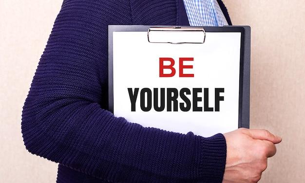 Be yourself steht auf einem weißen blatt, das von einem seitlich stehenden mann gehalten wird