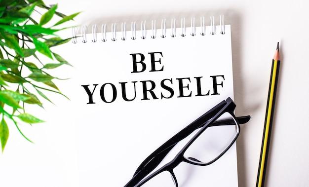 Be yourself steht in einem weißen notizbuch neben einem bleistift, einer schwarz gerahmten brille und einer grünen pflanze.