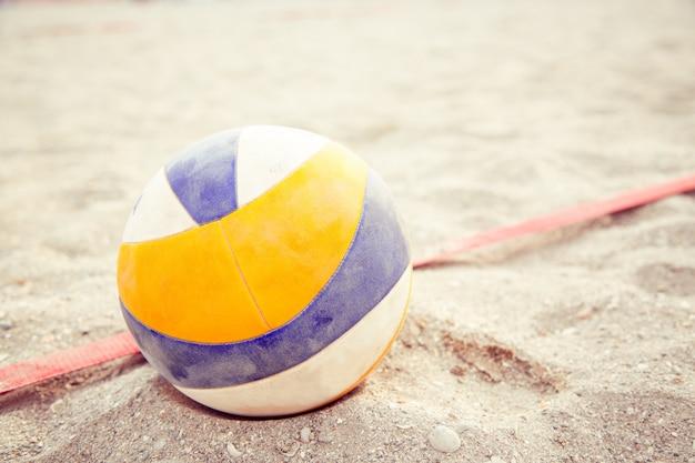 Beach-volleyball. spielball unter sonnenlicht und blauem himmel. volleyball im sand am strand