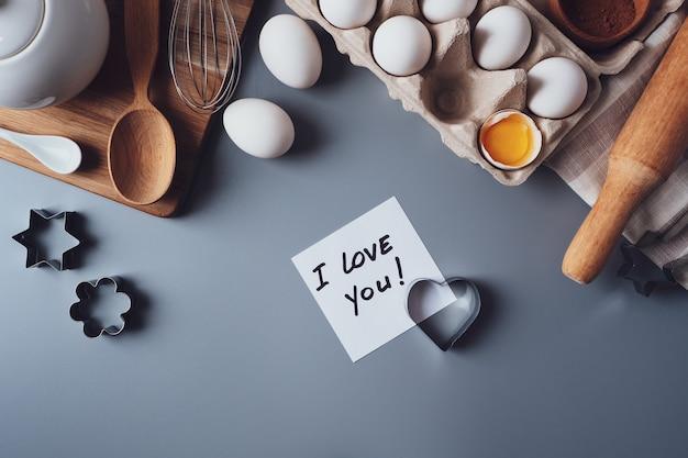 Beachten sie, dass ich dich liebe. zutaten für die herstellung von hausgemachten keksen auf grauem hintergrund. das konzept des kochens von süßigkeiten zum valentinstag, vatertag oder muttertag. flache lage, ansicht von oben.