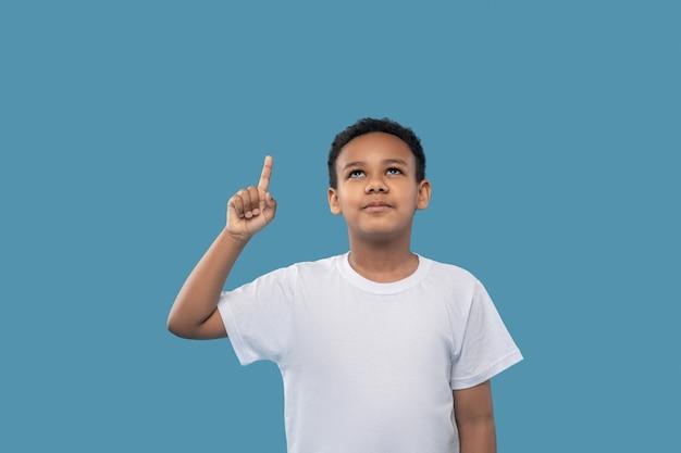 Beachtung. afroamerikanischer junge im weißen t-shirt hebt seine hand und zeigt in guter laune auf blauem hintergrund