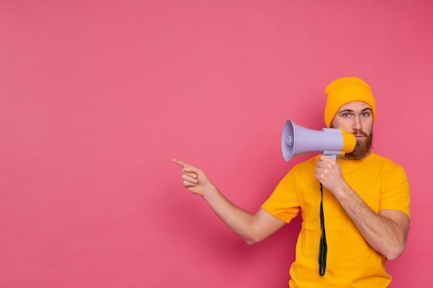 Beachtung! europäischer mann mit megaphon, der finger nach links auf rosa hintergrund zeigt