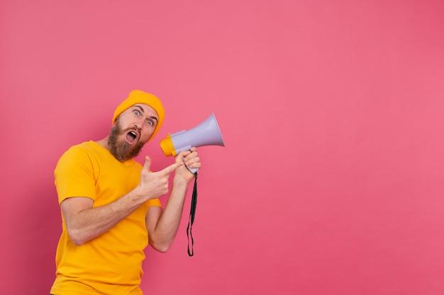 Beachtung! europäischer mann mit megaphon, der finger nach rechts auf rosa hintergrund zeigt