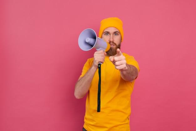 Beachtung! europäischer mann mit megaphon, der finger zur kamera auf rosa hintergrund zeigt