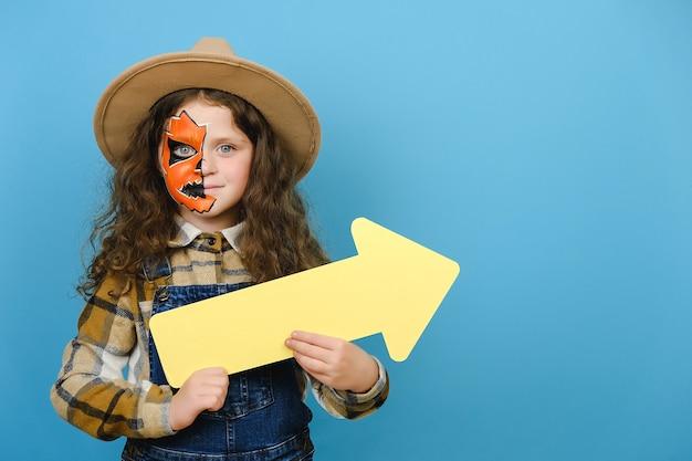 Beängstigend hell lebendiges kleines mädchen mit halloween-make-up-maske, die mit gelbem pfeil beiseite zeigt, trägt hut und hemd, modell über blauer studio-hintergrundwand mit kopienraum für werbeinhalte