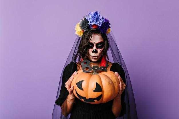 Beängstigende tote braut, die kürbis hält. europäische frau im schwarzen schleier, der auf lila wand in halloween aufwirft.