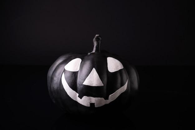 Beängstigender halloween-kürbis lokalisiert auf schwarz. gruselige gesichter süßes oder saures