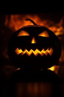 Beängstigender kürbis für halloween-feier auf dem hintergrund der flammen.