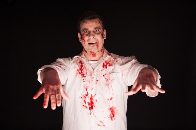 Beängstigender mann mit blutigen händen über schwarzem hintergrund. mann verbreitet terror.