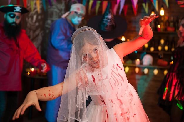Beängstigendes kleines mädchen auf einer halloween-party, verkleidet wie eine braut im jätkleid. furchtsamer pirat im hintergrund.