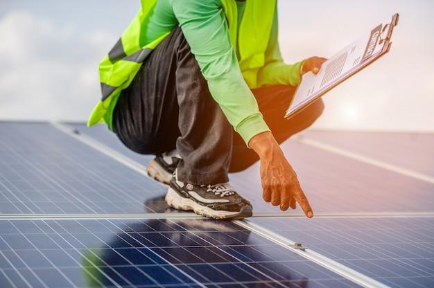 Beamte arbeiten an sonnenkollektoren, alternativer stromversorgung und bodenfläche. natürliche energie