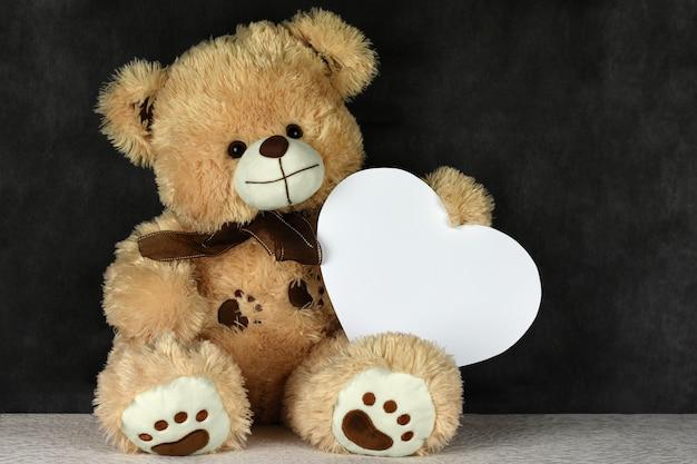 Bear teddy mit einem herzförmigen rahmen liebt dich am valentinstag
