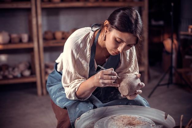 Beautifulyoung frau meister demonstriert den prozess der herstellung von keramikgeschirr mit der alten technologie. volkshandwerk.