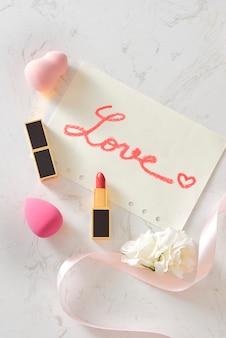 Beauty blender und lippenstifte mit liebesbrief