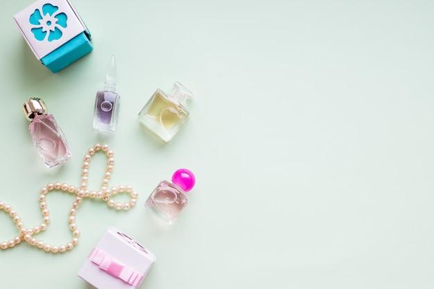 Beauty-blog-konzept. accessoires, geschenkboxen, kosmetik und schmuck auf pastellgrüner wand. frauentag konzept. glückliches frauentagstextzeichen. luxus teurer schmuck und make-up