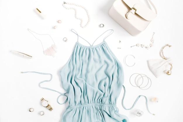 Beauty-blog-konzept. frauenkleidung und accessoires: blaues kleid, geldbörse, uhren, armband, halskette, ringe, lippenstift auf weißem hintergrund. flache lage, modischer weiblicher hintergrund der draufsicht.