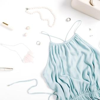 Beauty-blog-konzept. frauenkleidung und accessoires: blaues kleid, geldbörse, uhren, armband, halskette, ringe, lippenstift auf weißem hintergrund. flache lage, modischer weiblicher hintergrund der draufsicht. Premium Fotos