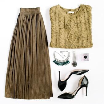 Beauty-blog-konzept. frauenkleidung und accessoires: grüner rock und pullover, uhren, halskette, schuhe auf weißem hintergrund. flache lage, modischer weiblicher hintergrund der draufsicht.