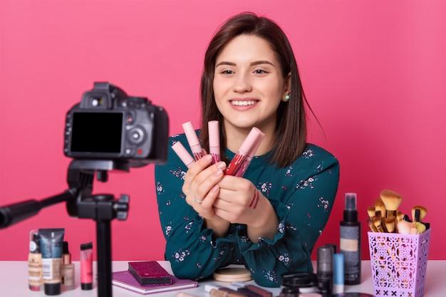 Beauty-blogger sitzt vor der kamera und wirbt für verschiedene lippenstifte für follower. online-übersetzung des tutorial-videos