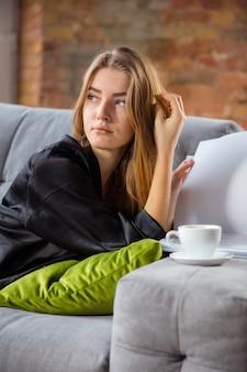 Beauty day für sich. frau, die seidengewand trägt, das ihre tägliche hautpflege-routine zu hause tut. auf dem sofa liegen, magazin lesen, kaffee trinken. konzept von schönheit, selbstpflege, kosmetik, jugend. nahansicht.