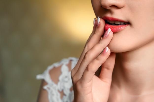 Beauty frau gesicht. studioporträt der schönen jungen sexy brunettefrau mit natürlichem make-up, haut und dem finger nahe perfekten geformten lippen auf schwarzem. getönten