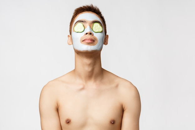 Beauty-, hautpflege- und spa-konzept. porträt des gutaussehenden entspannten asiatischen mannes mit nacktem oberkörper, der sich mit gesichtsmaske und gurken auf den augen entspannt, kopf anhebt, trost fühlt, stehende weiße wand
