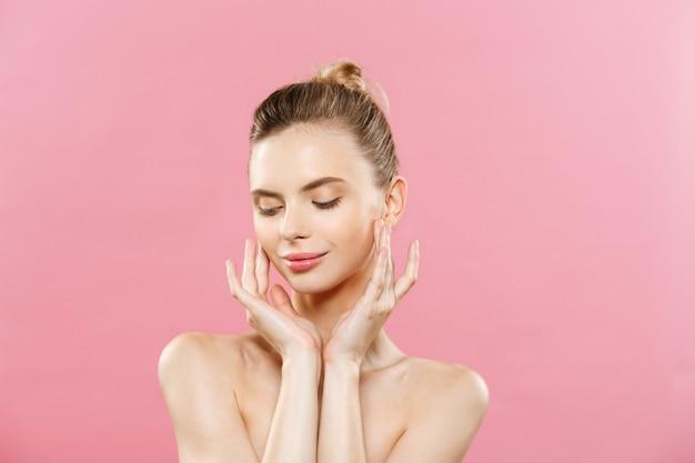 Beauty-konzept - schöne frau mit sauberen frischen haut close up auf rosa studio. hautpflege gesicht. kosmetologie.