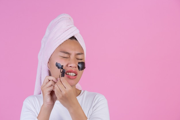Beauty kosmetisches peeling. junge frau mit schwarzem ziehen weg maske auf kosmetischem hautpflege-schalenprodukt der haut auf gesicht auf einem rosa ab.