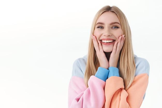 Beauty-, lifestyle- und modekonzept. nahaufnahmeporträt des fröhlichen, weiblichen blonden mädchens im hoodie hood