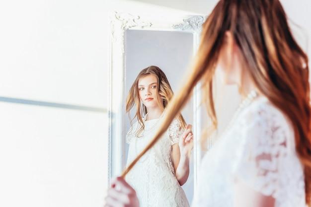 Beauty-make-up-morgen-rutine lieben sich selbst konzept. junge jugendliche, die reflexion im spiegel betrachtet. junge positive frau, die weißes kleid trägt, das im hellen hellen raum gegen weiße wand aufwirft.