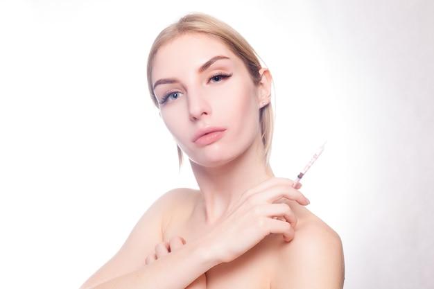 Beauty-, make-up- und people-konzept - attraktive junge frau bekommt kosmetische injektion, isoliert auf weißem hintergrund. ärztehände machen eine injektion ins gesicht. schönheitsbehandlung.