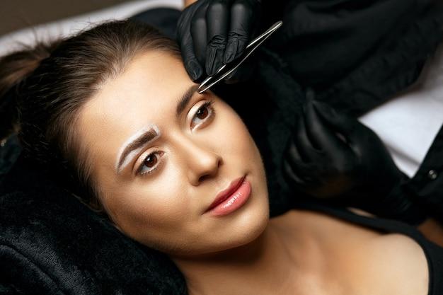 Beauty master korrigiert augenbrauen mit einer pinzette vor dem microblading